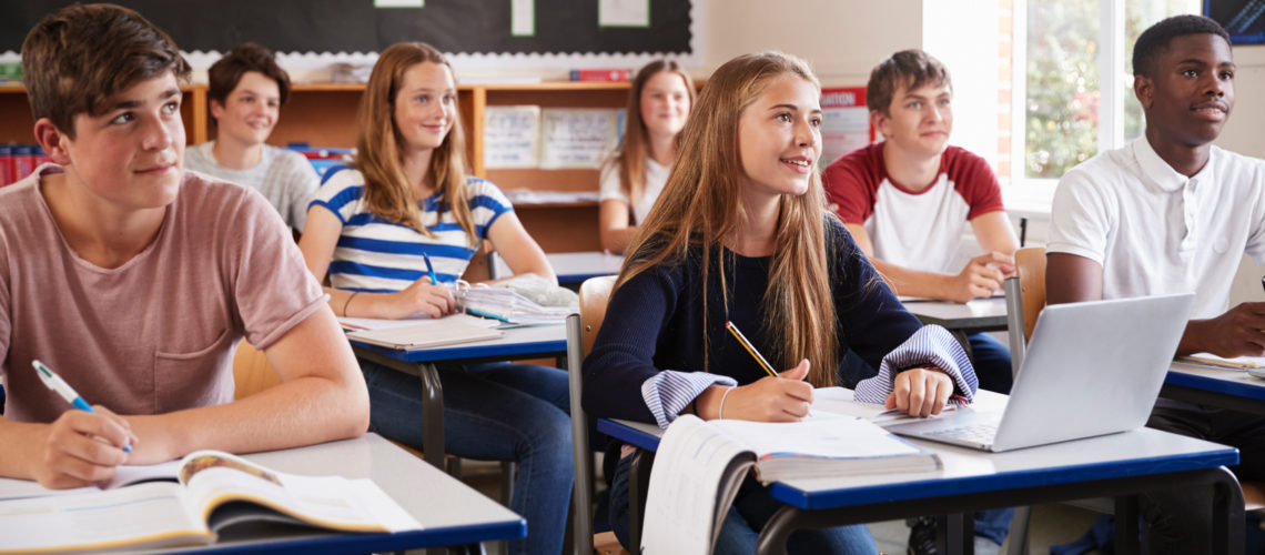 students-listening-to-female-teacher-in-classroom-PKHQXEN Copy